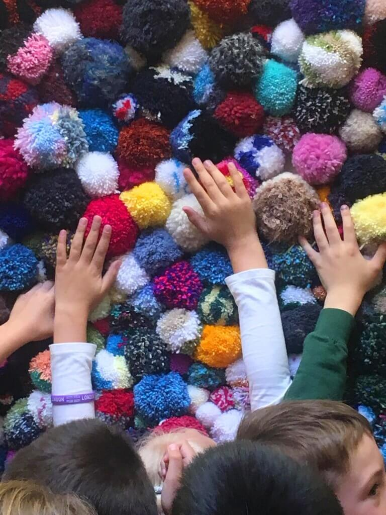 children feeling interactive pompom wall