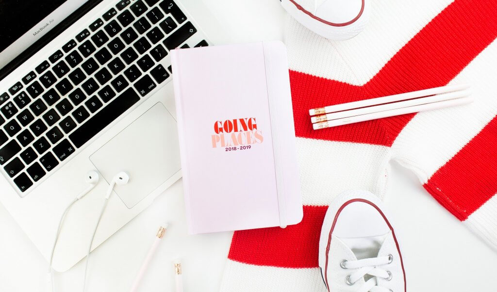 desk with planner and red striped sweater