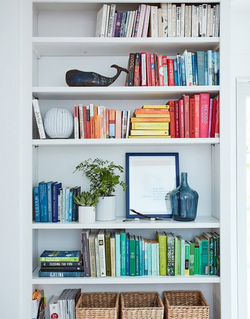 Image of color coded bookshelves in Ingrid Fetell Lee's home, showing a blue framed piece of art